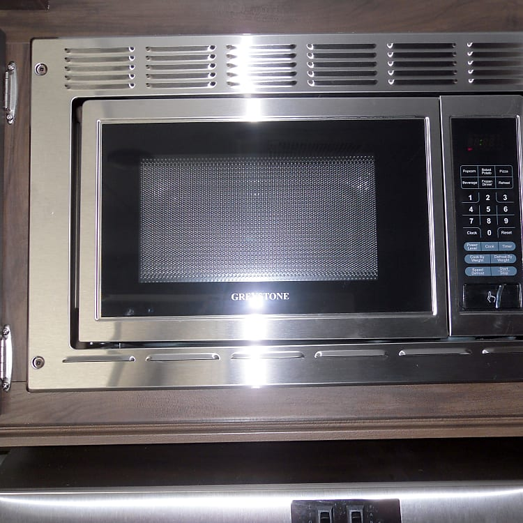 :Microwave above stove. The vent a hood is under the microwave above the 3 burner stove/oven