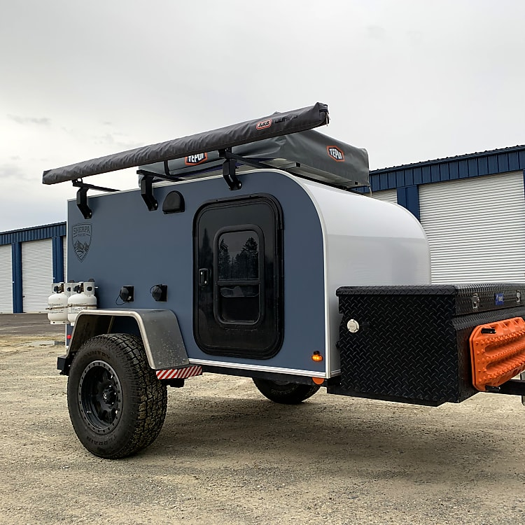 Adventure Trailer's comes equipped with side mounted propane tanks, front storage box for extra gear storage, 12vlt battery for inside lights and under trailer lighting, USB charging, Bluetooth Radio with TV-DVD player. For additional sleeping room a Tepui roof top tent is mounted on top of the trailer.