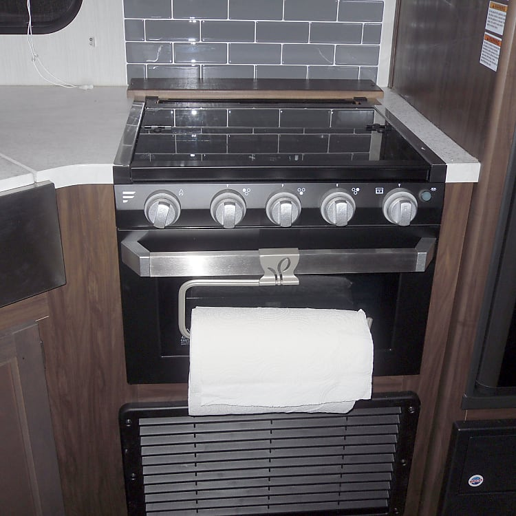 3 burner stove with glass topper cover, oven below and a paper towel rack. Refrig is to the right of the stove and the sink is to the left.