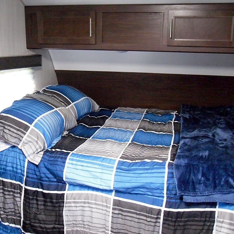 "Queen bed with 3"" memory foam topper. At the front of the unit, ""Sundarah"" (the RV unit)."
