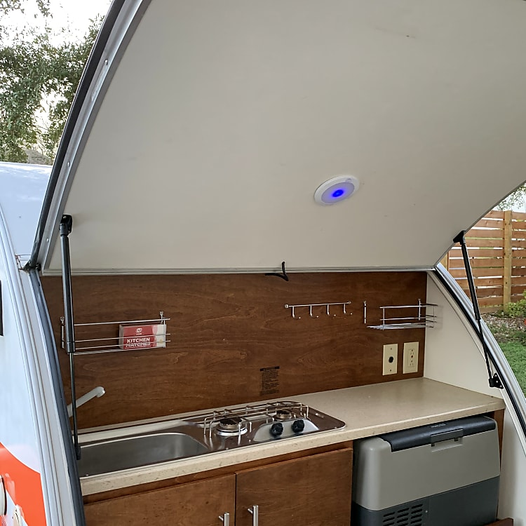 Kitchen in the trunk, with sink, two-burner propane stove, and Norcold refrigerator. Lid of trunk has lighting, and acts as cover from sun and rain.
