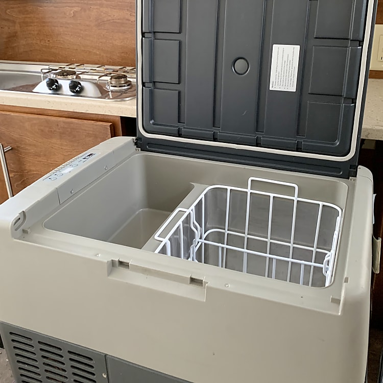 Close-up of new Norcold pull-out refrigerator. Works with DC or AC current. Will work in outside temperature ranges of 14—109 degrees F./This is located inside trunk at the back of the camper