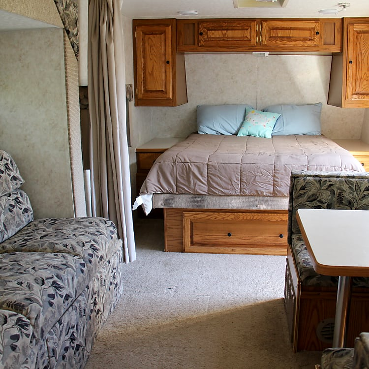 The main bed with the couch to the left that turns into a bed and the kitchen table to the right that turns into a bed.