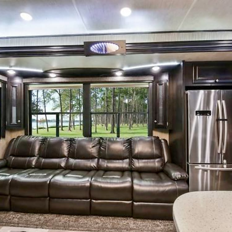 Luxurious living room Big windows and reclining massaging soft leather chairs with flip-down drink holders and USB chargers  and full-size refrigerator