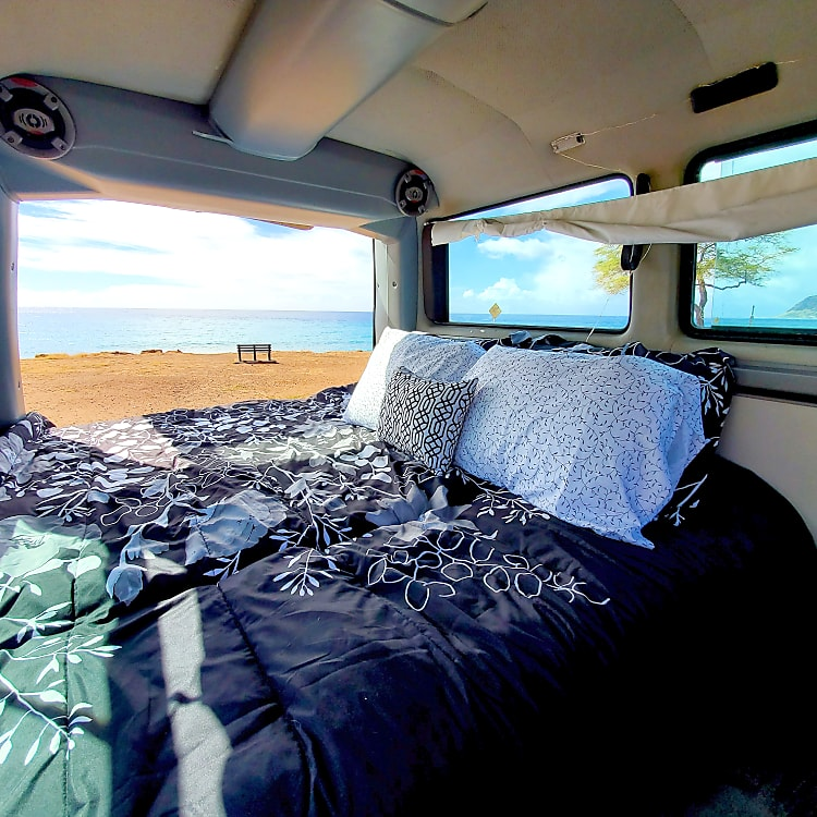 Back seat folds down into a bed.  Bedding, pillows and blankets are supplied. Windows have curtains for privacy.