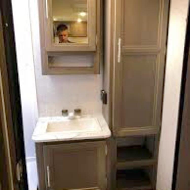 Bathroom vanity, medicine cabinet and large storage cabinet.