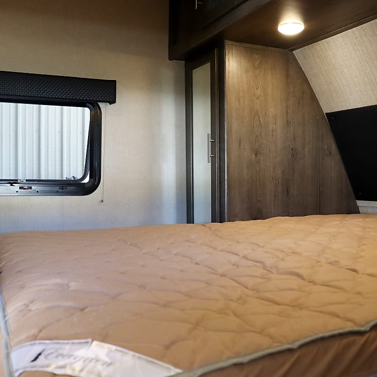 Queen bed in the bedroom with storage underneath.