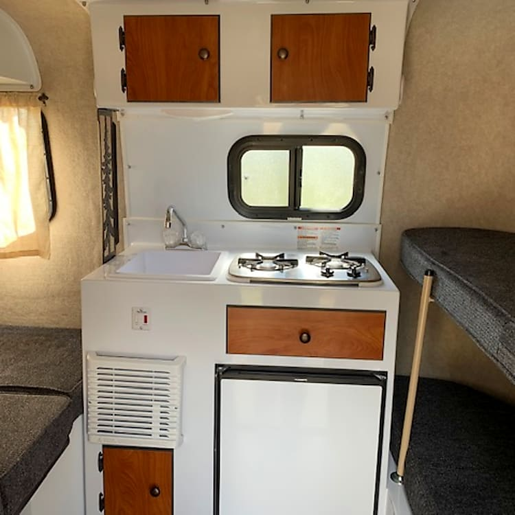 Kitchen area includes sink, 2 burner stove, and 3 way refrigerator (Can keep it on while driving!)