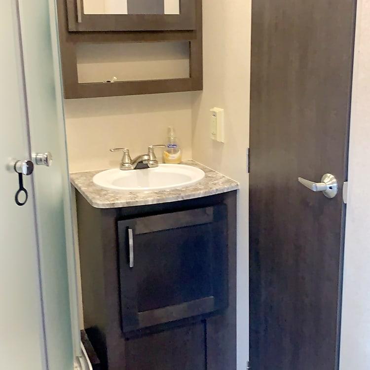 Bathroom: shower, toilet, sink and storage