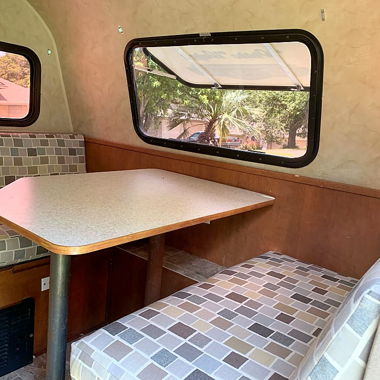Dining nook again. Front window closes when hauling to provide rock guard, but opens for a view and more light. The propane-fueled heater can be seen, below the far diner seat.
