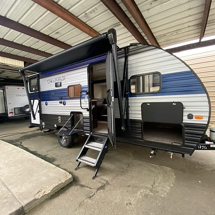 Side View showing Awning/Outdoor TV mount/Sturdy Step/Outdoor Fridge/Front Storage/Rear Bunk Storage Access.