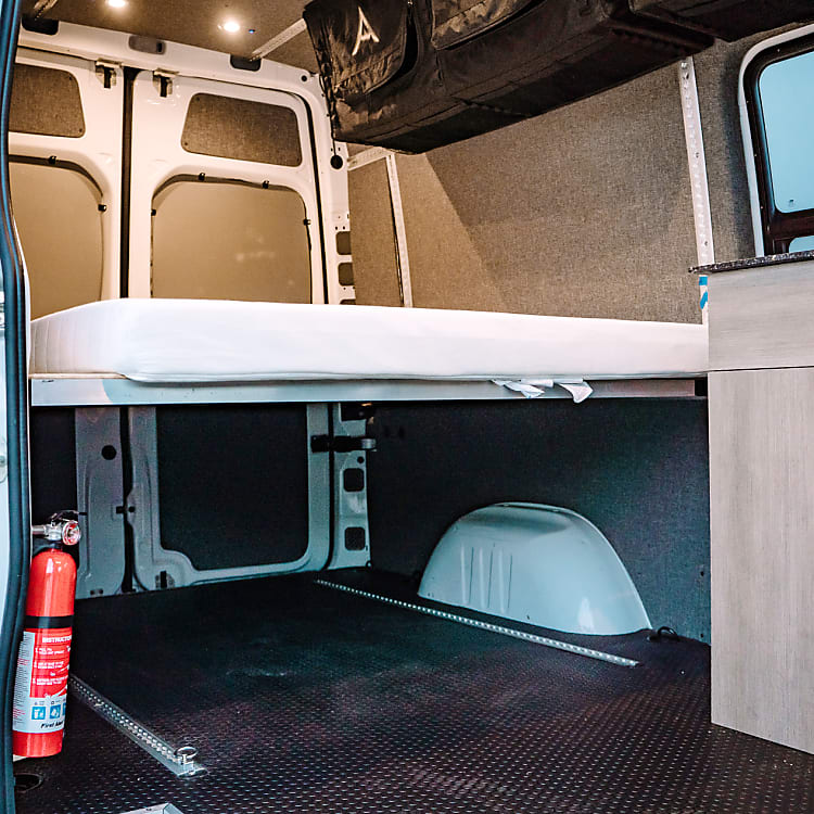 Large Queen-size bed with plenty of space under to carry lots of equipment.  Still not enough room, the bed can be raised to give more height.  L-Track provided to tie equipment or bikes down.