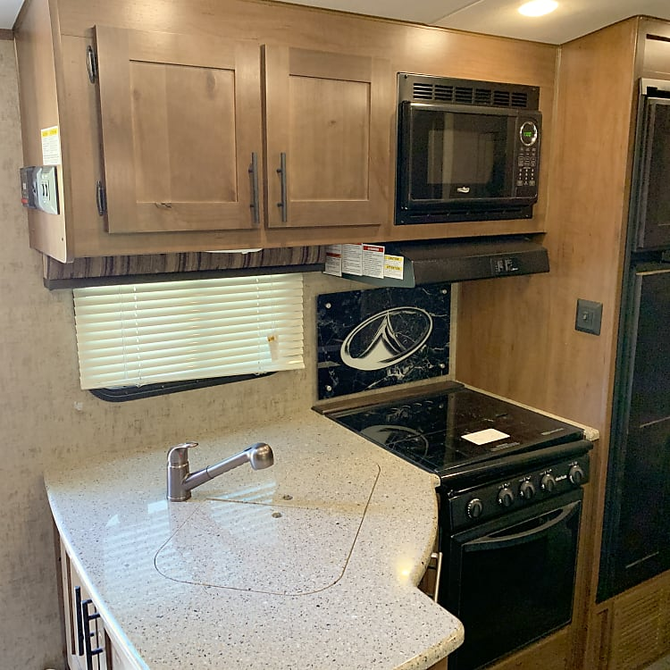 Double sink, Microwave, Stove, oven, Refrigerator and freezer.