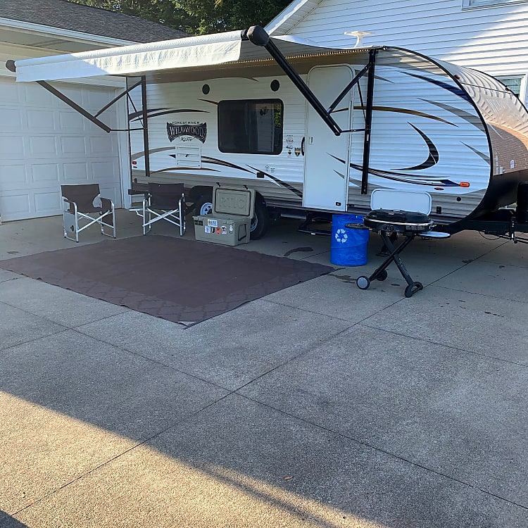 Rental includes 4 camping chairs (only two shown). Trash/recycling container for easy disposal of trash. Coleman road trip grill (propane adapter included). Camping all weather rug. RTIC 65 cooler. Picture shows LED under coach lights and under awning LED strip as well.