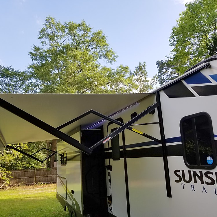 FROM THE FRONT WITH AWNING OUT AND LIGHTS ON