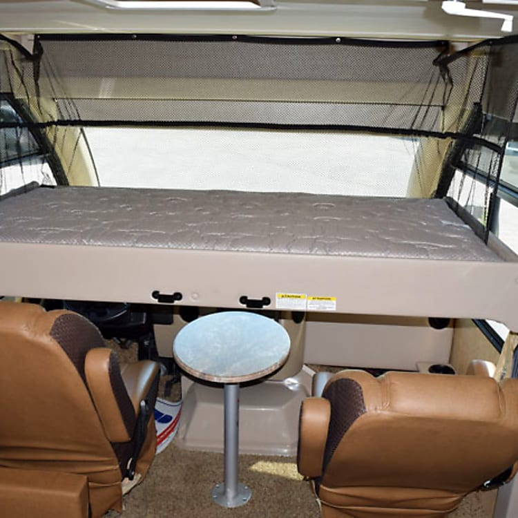 Overhead sleeping mattress over front captain chairs