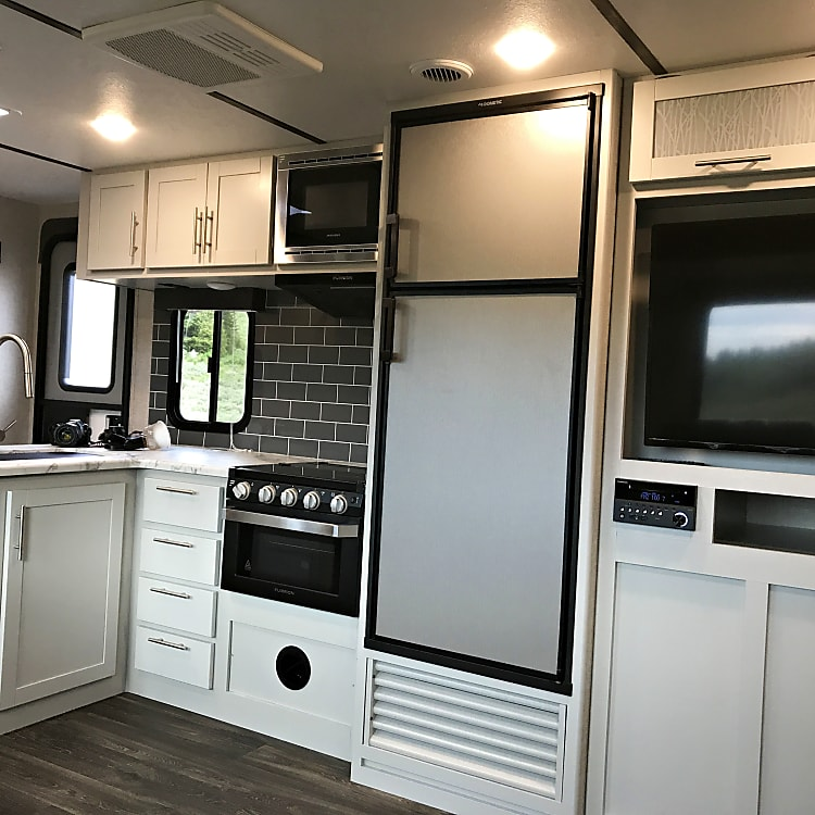 Fridge/freezer, stove/oven combo with large stainless steel sink.
