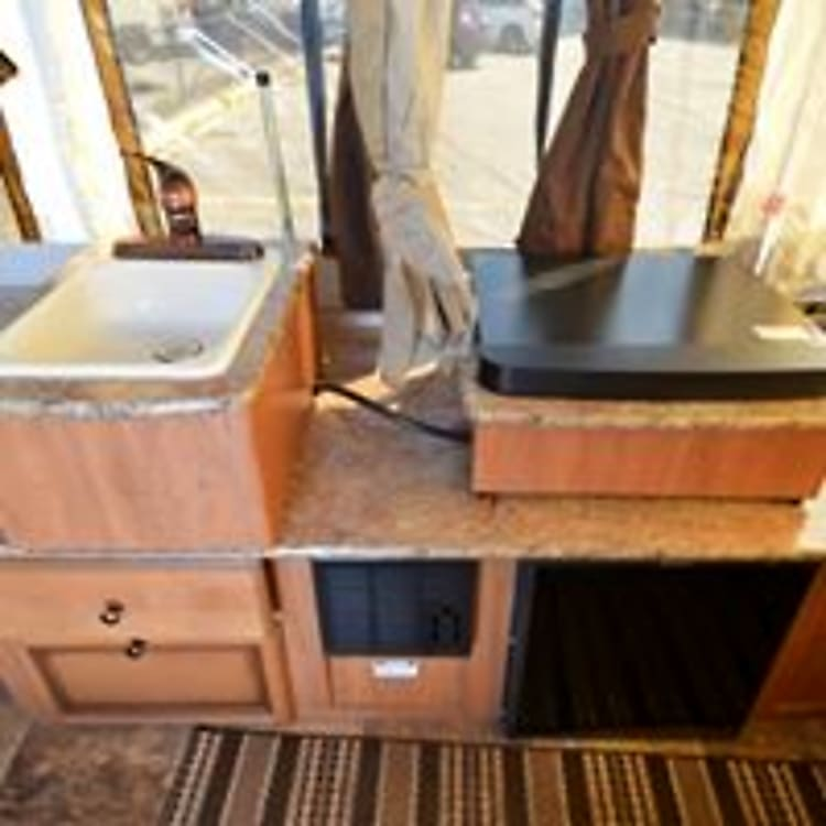 sink,stove top, refrigerator and heater pictured