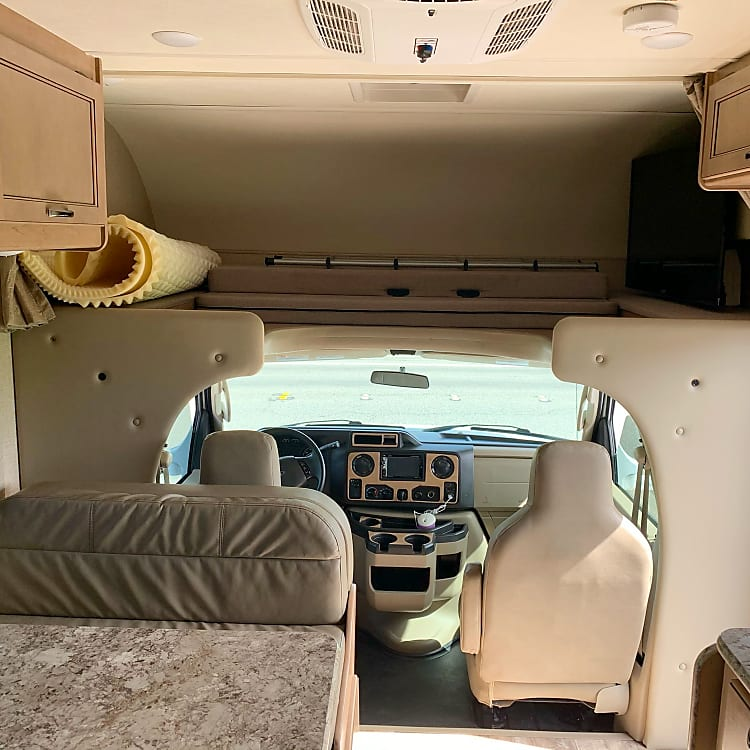front of the cab: plenty of storage in overhead cabinets, loft bed above driver/passenger seats with tv and satellite capabilities, plus AC unit above.