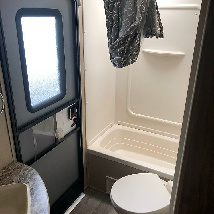 Bathroom with sink, toilet, and tub with shower