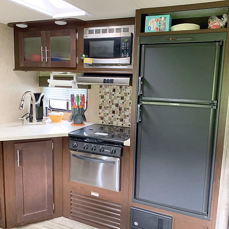 Gorgeous kitchen area equipped with a full kitchen utensil set, keurig w/complimentary k-cups, mixing bowls, cutting boards, coffee mugs and plastic dining set.