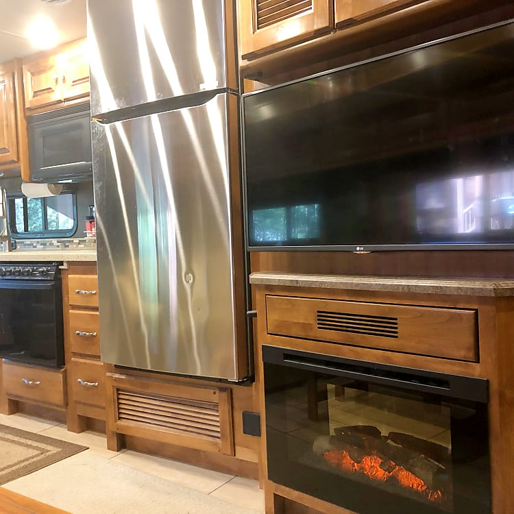 residential refrigerator with ice maker, TV above fireplace in living room