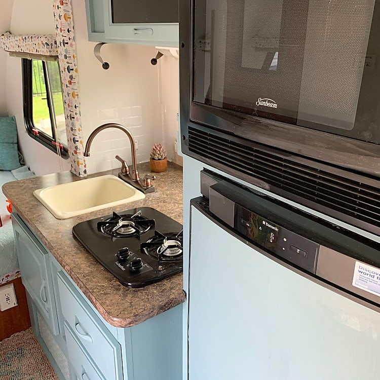 Functional kitchen with sink, microwave/convection combo, fridge and propane stove top.