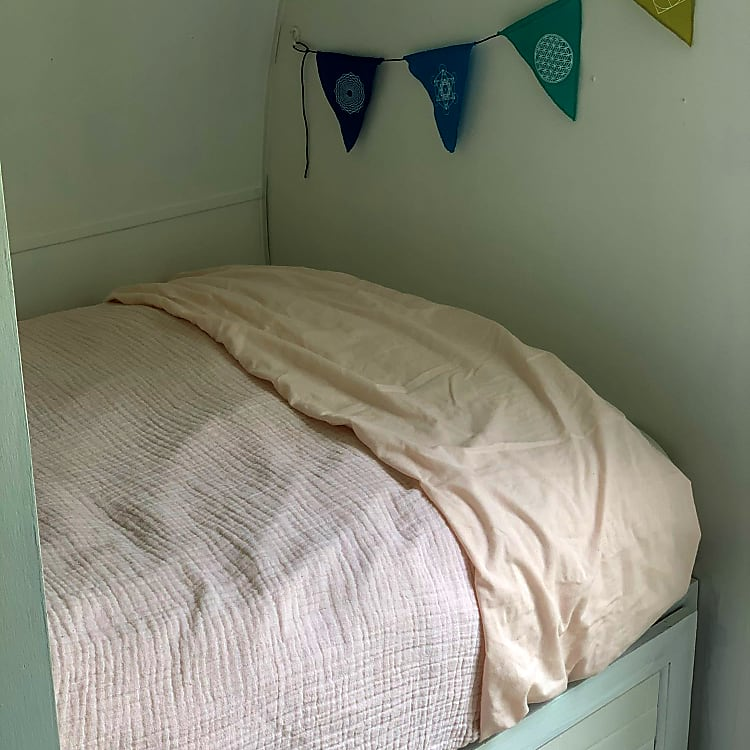Small second bed is perfectly cozy with a down filled featherbed.