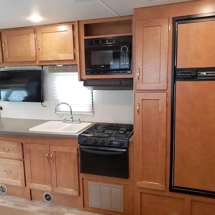 Full kitchen, including microwave, 3-burner stove, oven, refrigerator, and freezer.