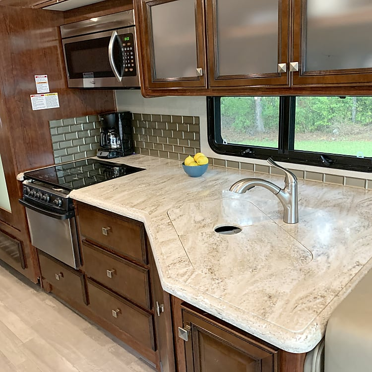 Full kitchen with countertop inserts to extend working space over the double sink and stove. Retractable faucet.