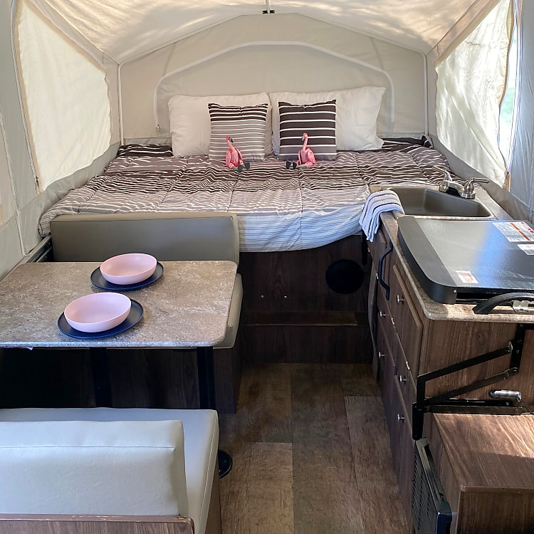 Full bed with kitchenette and dining table