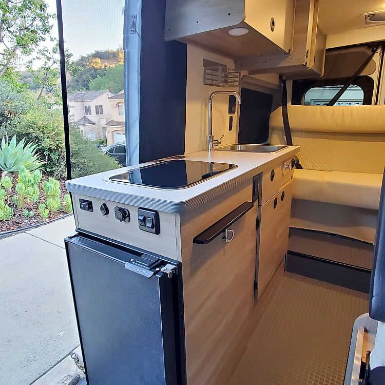 Large fully-stocked kitchen offers two burner cooktop, stainless steel sink & 12V refrigerator w/ freezer compartment