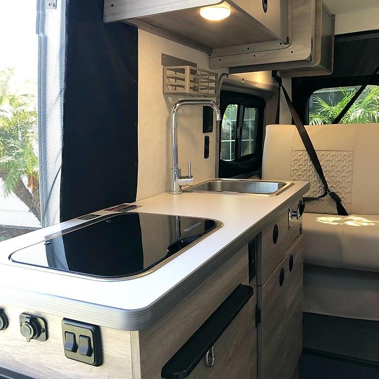 Kitchen Area (2 burner stove, refrigerator, sink, spice rack, cutting board and storage)