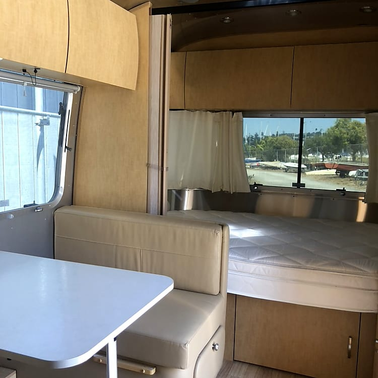 View of the bedroom (which sections off) and the dinette which drops into another comfortable sleeping options