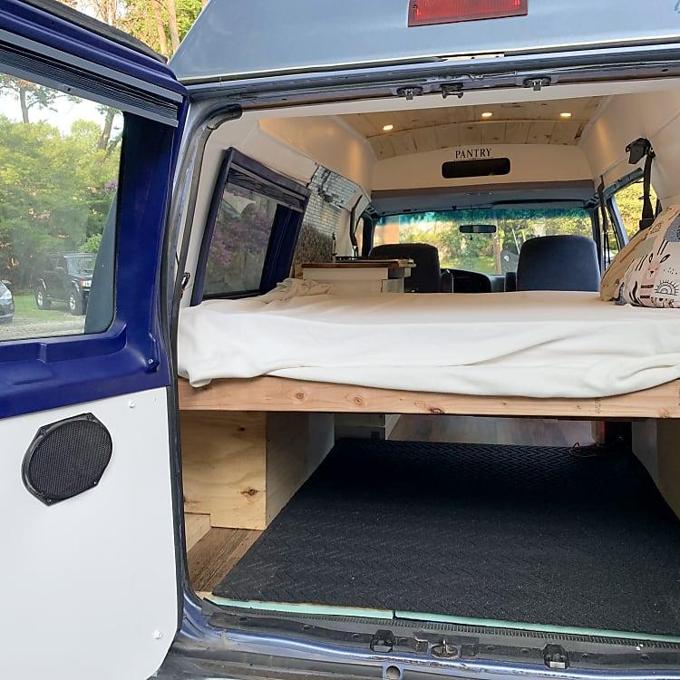 Back of van shows storage under bed for gear.