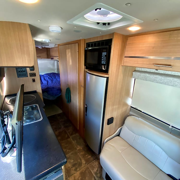 King size bed, restroom/shower, kitchen, loveseat/single bed, dining table, 2 TVs and swivel captain's chairs round out the living space.