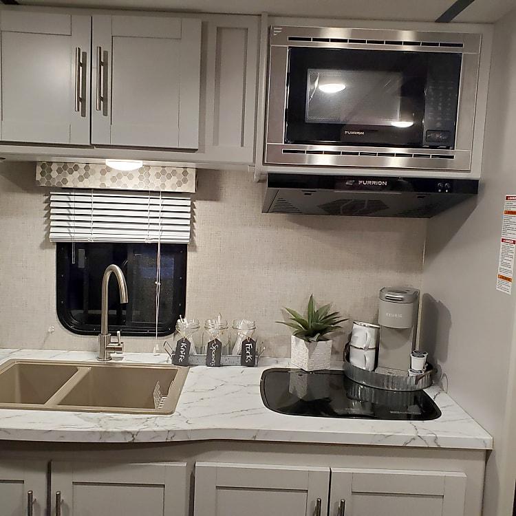 Sink, microwave, gas range, and coffeemaker