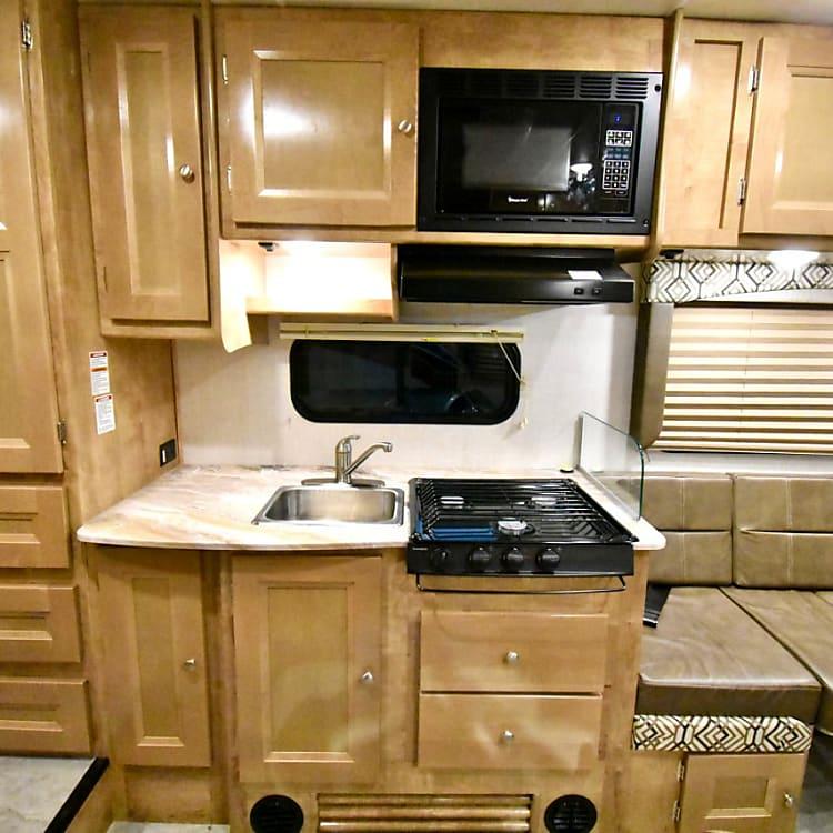 Kitchen area with a nice countertop, 3-burner stove, microwave, range hood, etc.