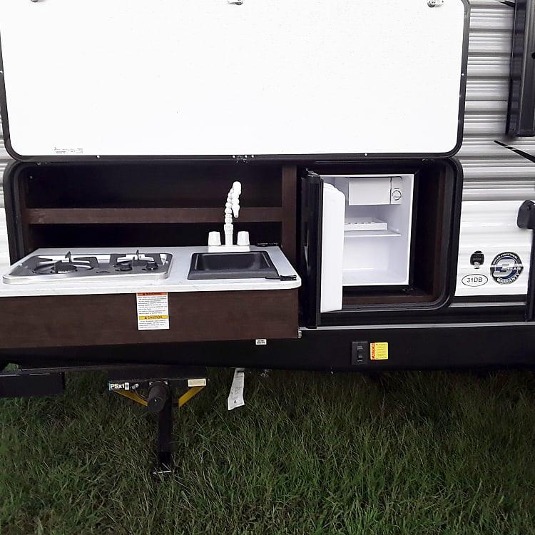 outdoor kitchen: stove, sink, and fridge/freezer