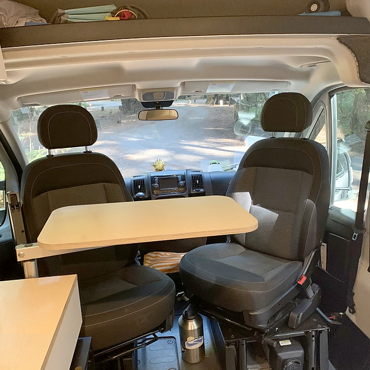 Swivel table is great for dining, extra counter space, or remote working. Captains chairs spin for in-van dining.