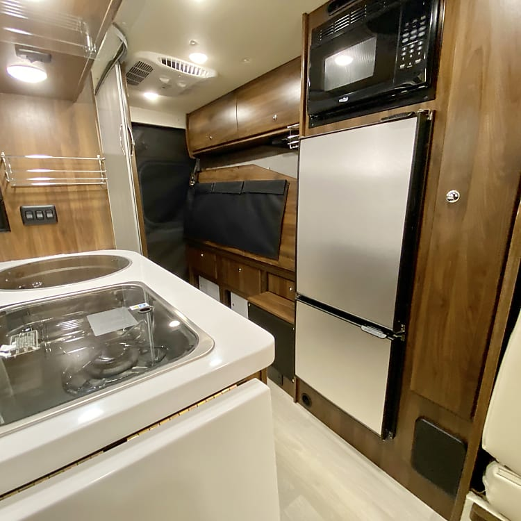 The kitchen is efficient with a full size refrigerator and freezer, microwave, two burner stove and sink.