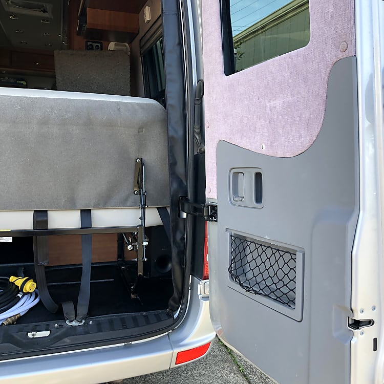 """Rear doors open either half way, or open onto the side of the RV. """"Trunk"""" contains water hose, power cord to shore power, TV cable, camp chairs, etc."""