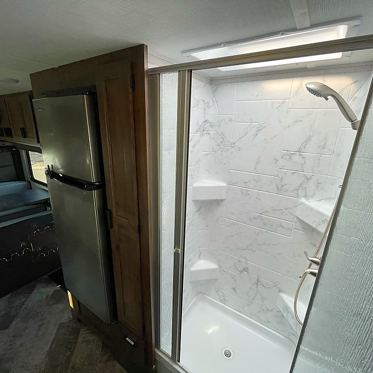 Roomy shower with extra headspace from skylight/fan
