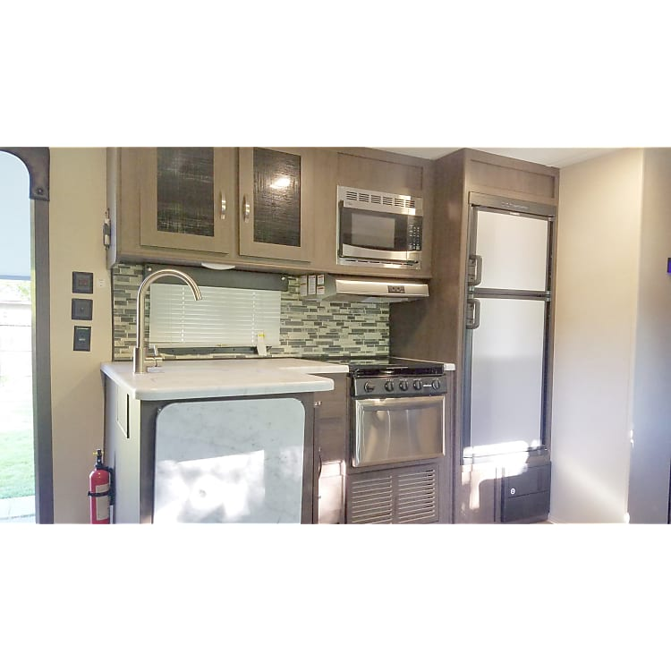 Kitchen features a refrigerator, freezer, microwave, 3 burner stove and oven, as well as a fold up counter top for additional room during food preparation.
