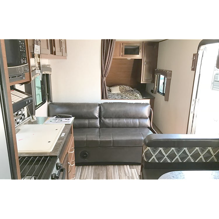 Featuring a pull-out jacknife sofa,4+ person dinette with folding table, and kitchen with oven, stove, & microwave.