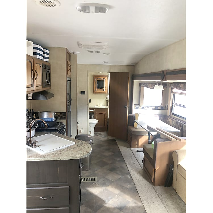 Looking to the back of the trailer. Couch on the right side, table, stove on the left side, sink, two bunk beds and straight back is the bathroom.