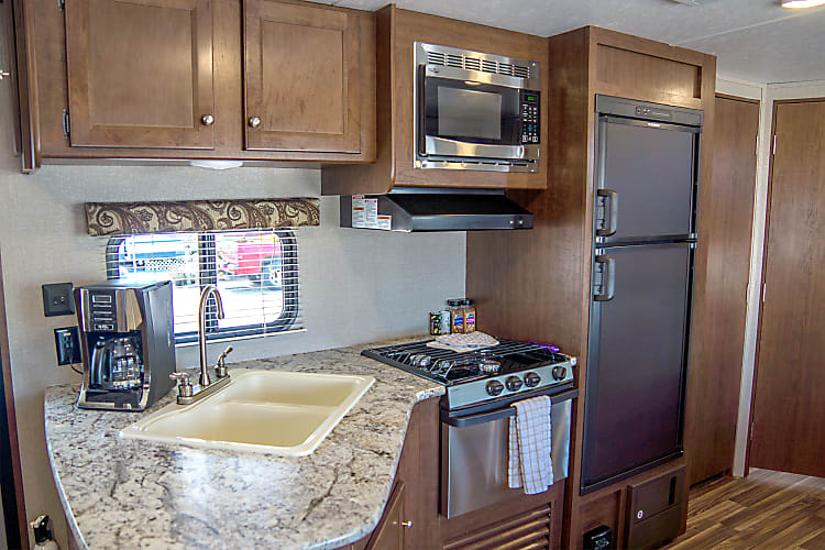 Large kitchen and refrigerator, with microwave , gas burners and stove, Coffee maker. Comes with all your Plates, cups, cooking utensils and much more. It is trip ready!
