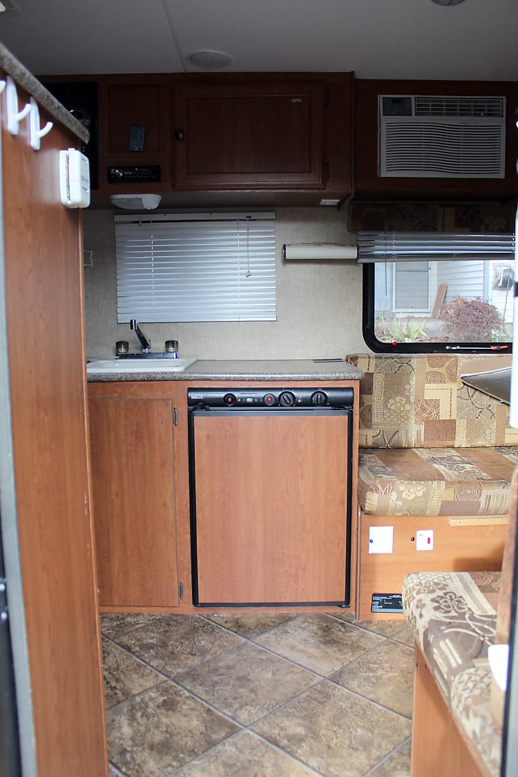 View from the entry door.  Dinette is on the right with A/C unit.  Large fridge with freezer.  Sink and stove are on the left.  Bunk beds and bathroom with shower is also on the left.
