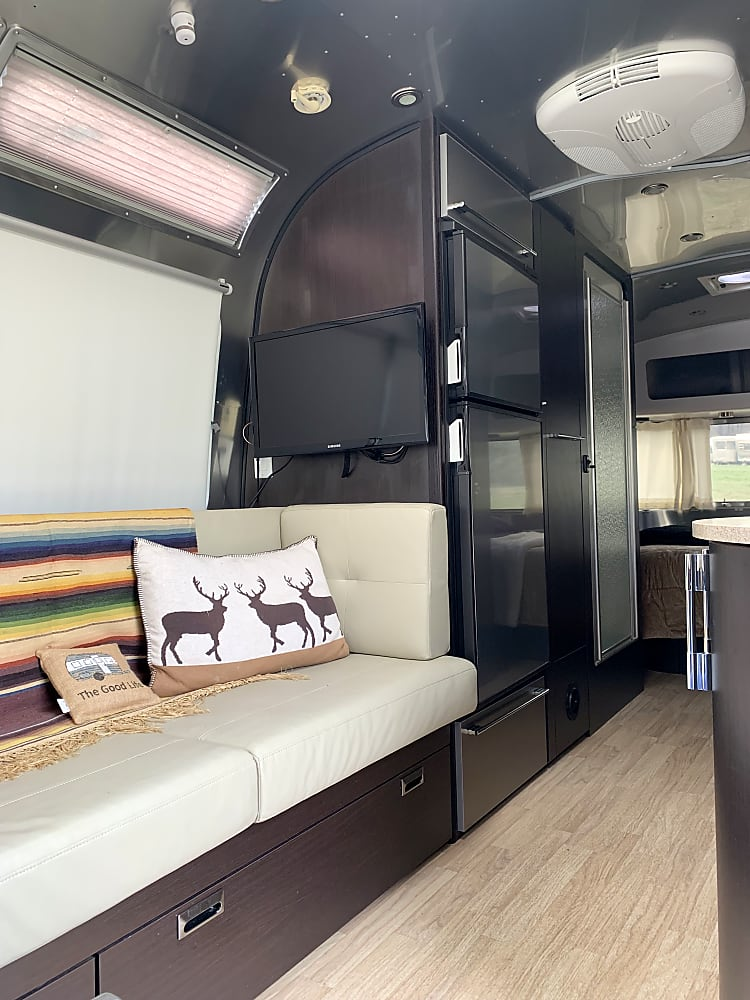 Beyond the dining area and first of two televisions is the refrigerator with freezer a large clothes closet and the shower room. The bedroom is at the back for the photo but the front of the trailer :)
