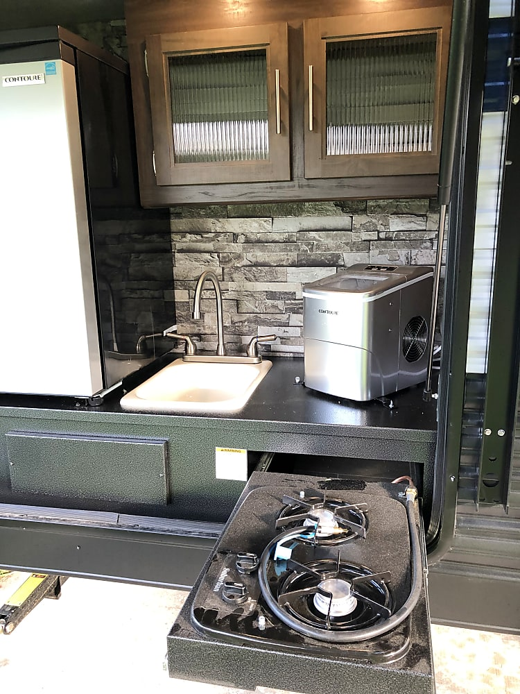 The outdoor kitchen includes large refrigerator, sink, icemaker and two burner stove